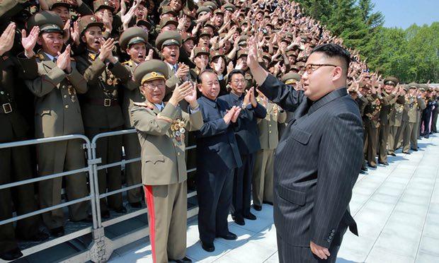 Coreea de Nord a lansat o rachetă. Când vine apocalipsa? Kim Jong-un (front right) waves to North Korean rocket developers in a photograph released on Saturday. Photograph: STR/AFP/Getty Images